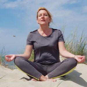 Helga mediteert op een duin op Vlieland tijdens workation